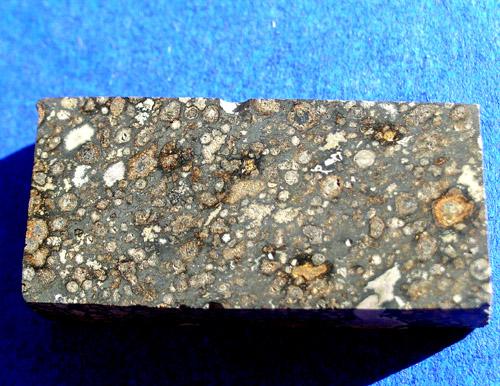 Axtell-CV3. Nieźle widoczne chondry, wraz z typowym dla chondrytów węglistych - ciemnym wnętrzem. Źródło zdjęcia:   http://www.meteoritehunter.com/