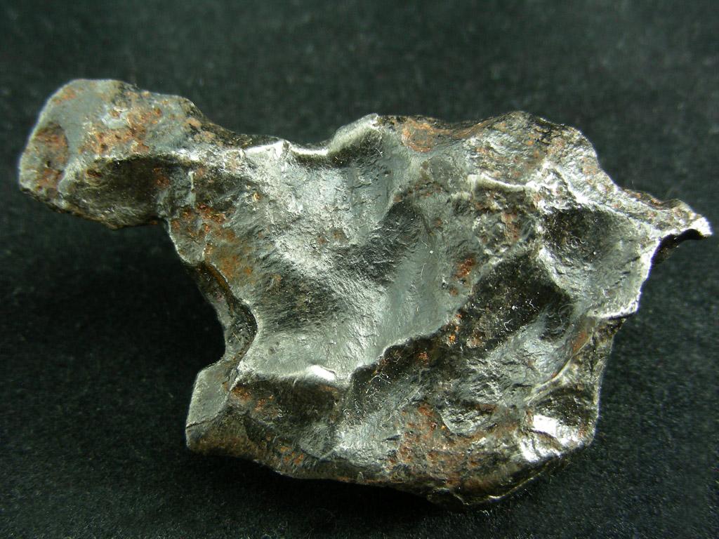 Sikhote Alin - żelazny. Ładne regmaglipty, nieregularnie pokrywające ten okaz meteorytu żelaznego. Źródło zdjęcia:   http://www.carionmineraux.com/